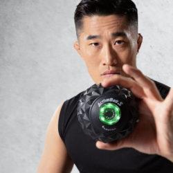 Guy holding a vibrating massage ball for photoshoot