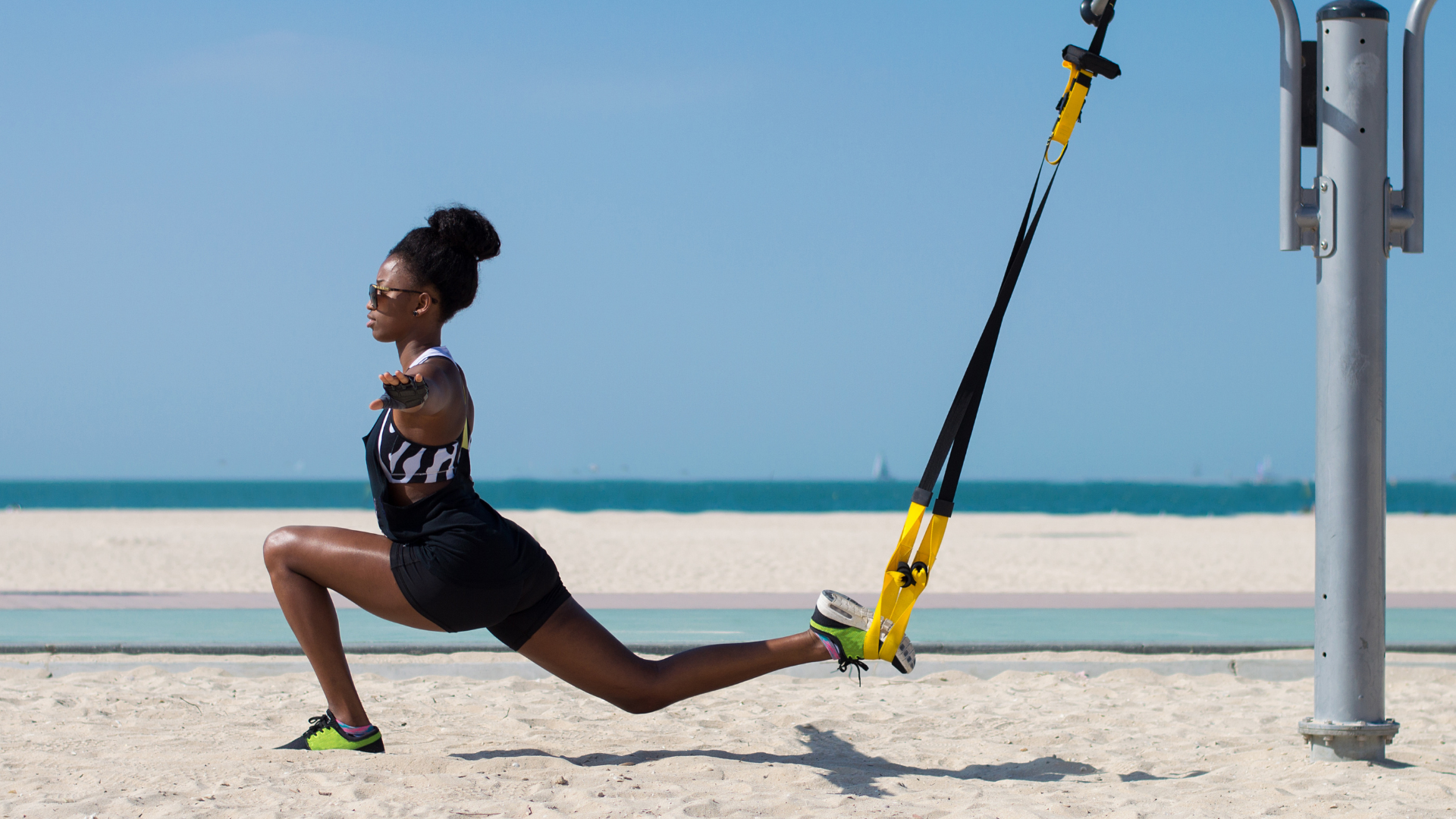 athlete balancing with the help of suspension trainer Australia beach
